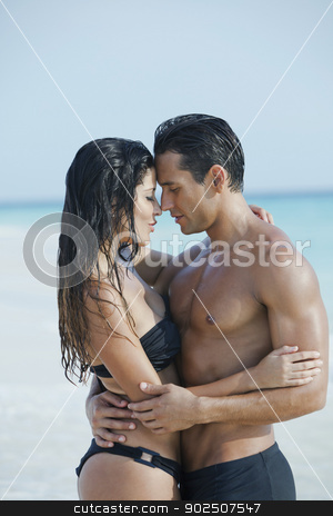 Couple romancing on the beach stock photo, Couple romancing on the beach day time by Gabriela Medina