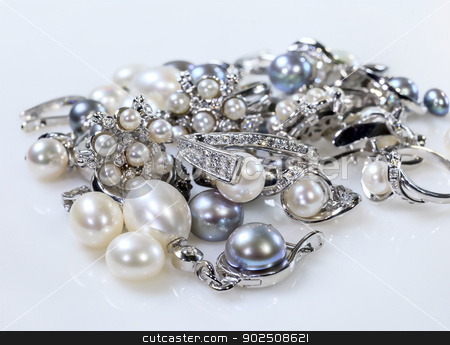 Rings and earrings with pearls stock photo, A set of two rings and earrings with pearls. Objects lying on a white table surrounded by pearls of different colors. by fogen