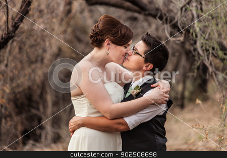 Lesbian Couple Kissing in the Woods stock photo, Happy same sex newlyweds kissing in the woods by Scott Griessel