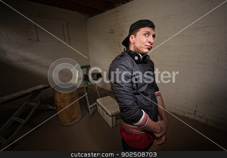 Rapper with Folded Arms stock photo, Urban musician with arms folded in basement by Scott Griessel