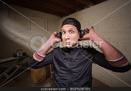 Surprised Man with Earphones stock photo, Surprised young man holding earphones over ears by Scott Griessel