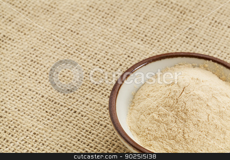 baobab fruit powder stock photo, small ceramic bowl of African baobab fruit powder against burlap canvas with a copy space by Marek Uliasz