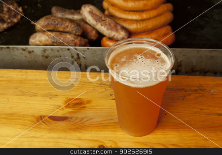 Beer stock photo, A plastic glass of beer over a wooden table, with sausages ont he back by Fabio Alcini