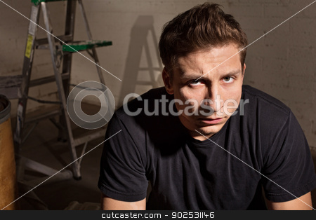 Angry Male with Ladder stock photo, Angry young white man with ladder in background by Scott Griessel