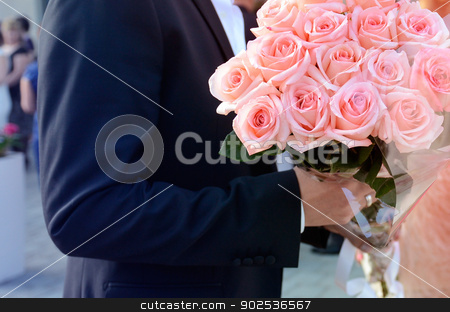 Man holding bouquet in hands stock photo, Man holding imense roses bouquet in hands for a nice woman. by ifeelstock