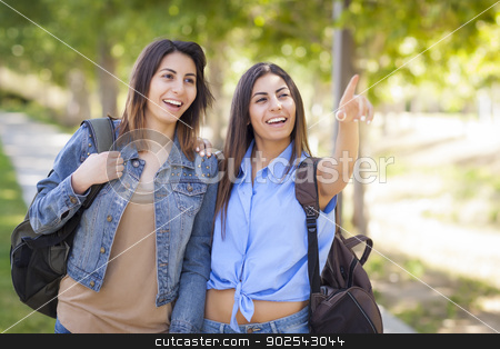 Mixed Race Twin Sisters Wearing Backpacks and Pointing Outside stock photo, Young Adult Mixed Race Twin Sisters Wearing Backpacks and Pointing Outside. by Andy Dean