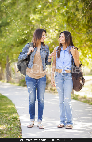 Young Adult Mixed Race Twin Sisters Walking Together stock photo, Young Adult Mixed Race Twin Sisters Walking Together Wearing Backpacks Outside. by Andy Dean