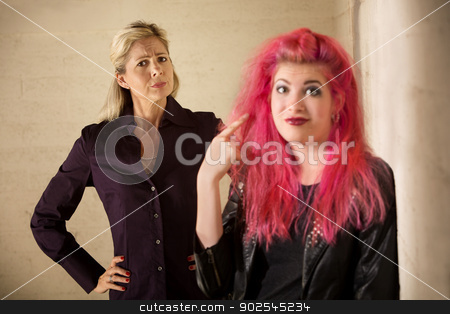 Child Ignoring Parent stock photo, Gullible mother behind teenage girl pointing to ear by Scott Griessel
