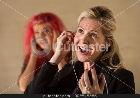 Obnoxious Woman Listening to Music stock photo, Goofy Caucasian lady with mp3 player and annoyed teenager by Scott Griessel