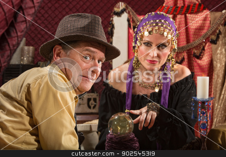 Nervous Man Gets Fortune stock photo, Beautiful fortune teller in head scarf and nervous male customer by Scott Griessel