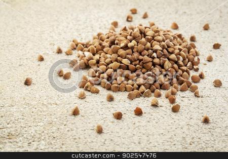 backwheat grain kasha stock photo, a roasted buckwheat grain  (kasha) on a rough white painted barn wood background by Marek Uliasz