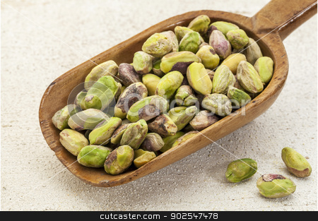 raw pistachio nuts on a scoop stock photo, a wooden scoop od raw pistachio nuts on a rough white painted barn wood background by Marek Uliasz
