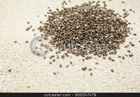 chia seeds stock photo, a pile of black chia seeds on a rough white painted barn wood background by Marek Uliasz