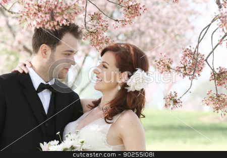 Wedding Couple Under Cherry Blossoms stock photo, A young 20 something bride and groom hold each other close in a loving embrace. Photograph features a cherry blossom background by Kim Wilson