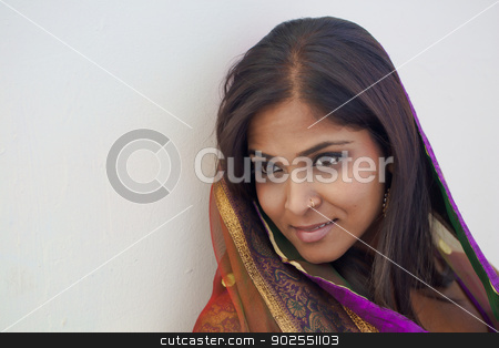 Intimate Portrait on An Indian Woman stock photo, A young, modern, 20 something, Indian woman with long black hair, dressed in a purple and gold traditional Indian sari, rests her head against a white wall for an intimate, close up portrait  by Kim Wilson
