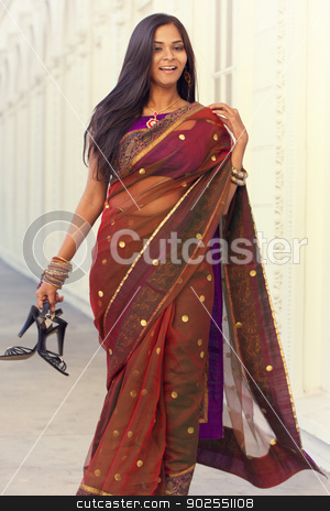 Vintage Elegance stock photo, A young, modern, 20 something, Indian woman with long black hair, dressed in traditional Indian attire (sari), holds her shoes as she walks down a long white hallway with repetitive arches, processed for a slight vintage effect by Kim Wilson
