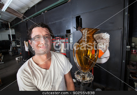 Man Holding Finished Vase stock photo, Handsome Hispanic man holding yellow vase on rod by Scott Griessel