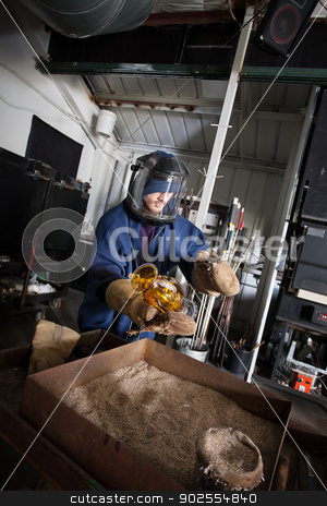 Worker With Glass Vase stock photo, Young glass worker in protective suit and helmet with hot jar by Scott Griessel
