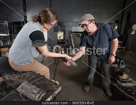 Two People Shaping Glass stock photo, Glass artisan helping young student create glass vase by Scott Griessel