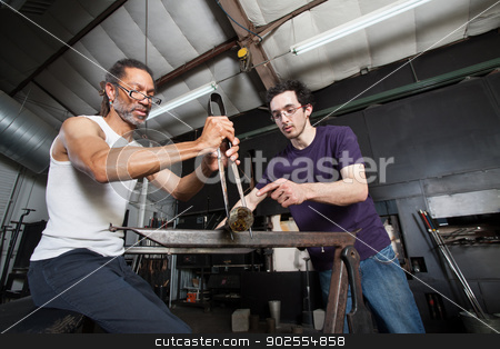 Glass Manufacturing Teamwork stock photo, Assistant helping glass manufacturing worker with pliers by Scott Griessel