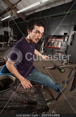 Glass Worker at Workbench stock photo, Serious young adult with tools and workbench in glass factory by Scott Griessel