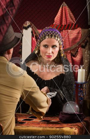Lady Dealing Tarot Cards stock photo, Charming fortune teller giving man a tarot card by Scott Griessel