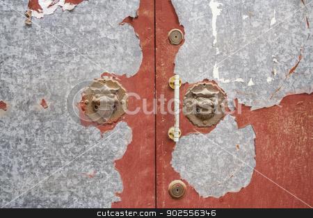 Lion Door Handles in a Beijing Hutong stock photo, Lion Door Handles on weathered door in a Beijing Hutong by Bryan Mullennix