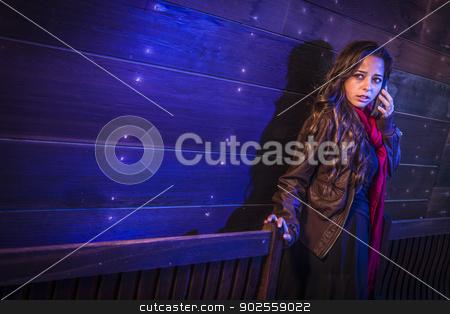 Frightened Young Woman in Dark Walkway Using Cell Phone stock photo, Frightened Young Woman in Dark Walkway Using Cell Phone at Night. by Andy Dean
