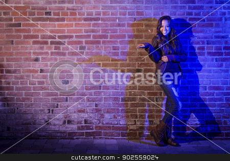 Mixed Race Woman Holding Her Hand Out Against Brick Wall stock photo, Portrait of a Pretty Mixed Race Young Adult Woman Holding Her Hand Out Against a Brick Wall with Plenty of Copy Space. by Andy Dean