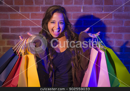 Mixed Race Young Woman Holding Shopping Bags Against Brick Wall stock photo, Excited Pretty Mixed Race Young Adult Woman Holding Shopping Bags with Brick Wall Background. by Andy Dean