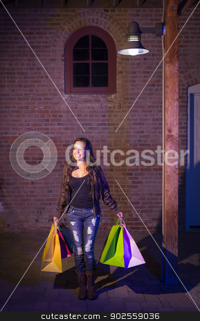 Mixed Race Young Woman Walking Carrying Shopping Bags at Night stock photo, Excited Pretty Mixed Race Young Adult Woman Walking in the Evening Holding Shopping Bags with Brick Wall Background. by Andy Dean