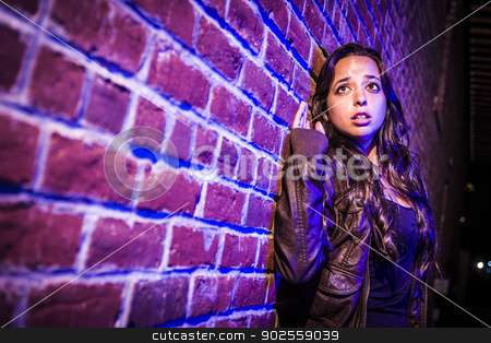 Frightened Pretty Young Woman Against Brick Wall at Night stock photo, Frightened Pretty Young Woman Against a Brick Wall at Night. by Andy Dean