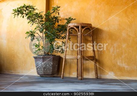 Simple interior design scene  stock photo, Simple interior design scene with rattan chair and  small tree on yellow wall by nalinratphi