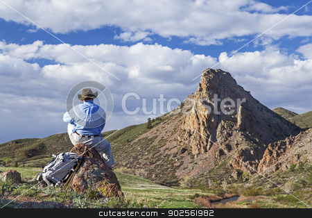 loneliness in mountains stock photo, a lonely hiker sitting and conteplating mountain scenry in springtime- Eagle Nest Open Space near Fort Collins, Colorado by Marek Uliasz