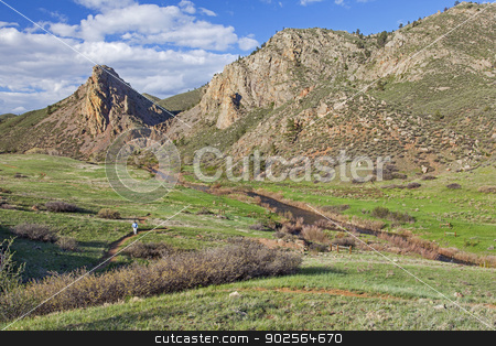 hiker in mountain scenery stock photo, a lonely male hiker in a vast mouintain ranch scenery - Eagle Nest Rock Open Space in Colorado at springtime by Marek Uliasz
