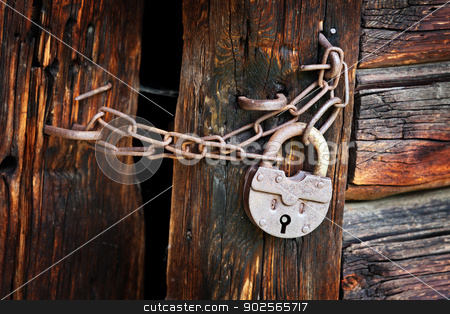 Old rusty padlock on rural wooden gate stock photo, Old rusty padlock and chain on the rural wooden gate by Alexey Romanov