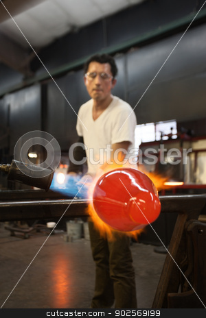 Man Blasting Glass with Flames stock photo, Glass factory worker forming glass object on flame by Scott Griessel
