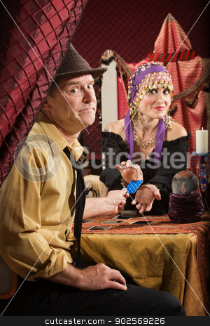 Man Paying Fortune Teller stock photo, Fortune teller receiving credit card from skeptical customer by Scott Griessel