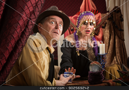 Frightened Tea Leaves Reader stock photo, Cursed mature man with gypsy woman reading tea leaves by Scott Griessel