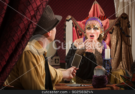 Fortune Teller Predicting Bad Luck stock photo, Frightened European female fortune teller looking at card by Scott Griessel