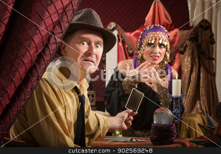 Upset Man with Tarot Cards stock photo, Disgruntled man holding tarot card with nervous fortune teller by Scott Griessel