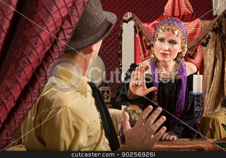 Gypsy Holding the Evil Eye stock photo, Calm gypsy woman waving hand over crystal ball by Scott Griessel