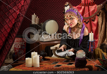 Sly Lady with Tarot Cards stock photo, Smiling gypsy soothsayer with hand of tarot cards by Scott Griessel
