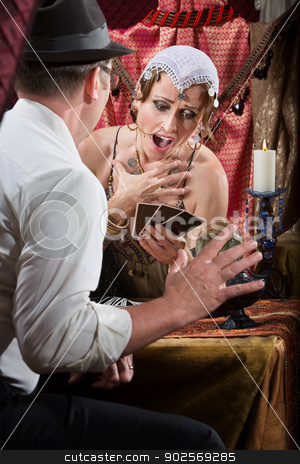 Shocked Tarot Card Reader stock photo, Shocked fortune teller holding tarot cards at table by Scott Griessel