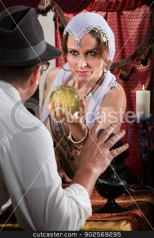 Pretty Fortune Teller Holding Crystal Ball stock photo, Fortune teller holding crystal ball in front of scared man by Scott Griessel
