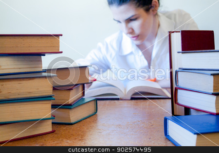 Catching up on some studies stock photo, Young girl reading very focused a book by Javier Correa