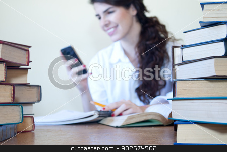 Receiving a funny text stock photo, Young woman reading a funny text message while studying by Javier Correa
