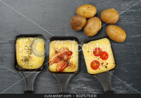 Raclette trays and potatoes stock photo, Photo of a three Raclette trays with melted cheese, herbs, cherry tomato, bacon, onion and potatoes on rough slate. Plenty of space for text. by © Ron Sumners