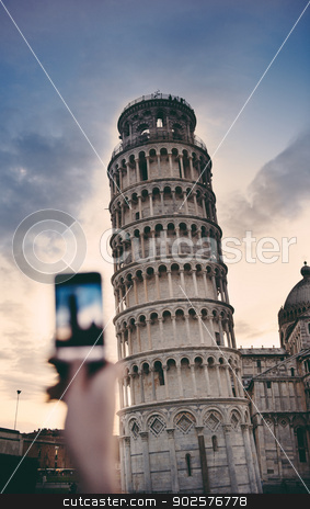 Tourist taking a photo at the Pisa Tower stock photo, Tourist takes snapshots with smartphone digital camera of Pisa Tower at the entrance to Piazza dei Miracoli on a cold summer evening. by ifeelstock