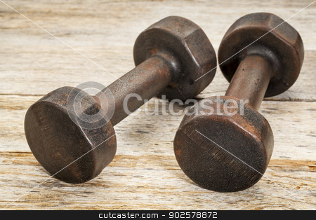 vintage iron dumbbells stock photo, a pair of vintage iron rusty dumbbells on white painted barn wood background - fitness concept by Marek Uliasz